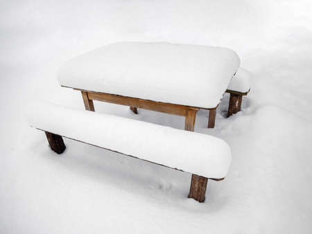 The benches and table are covered with snow in winter