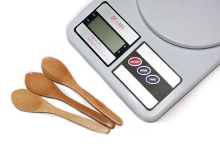 Digital kitchen scale with wooden spoons photo
