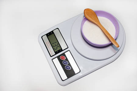 Digital kitchen scale with sugar in the bowl photo