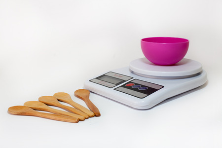 empty bowl: Digital kitchen scale with empty bowl and wooden spoons