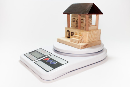 Wooden house on digital scale photo