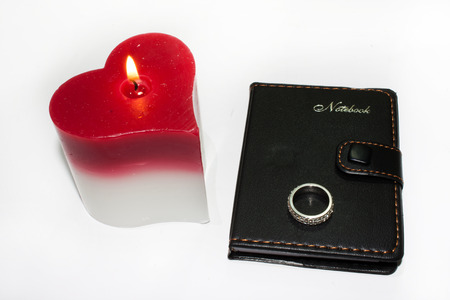 diamond candle: Heart candle and wedding ring on the notebook