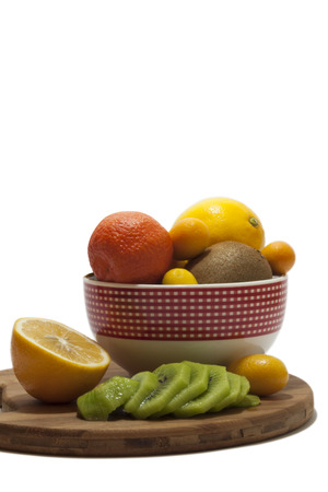 cumquat: Fruit arrangement in the bowl and on the kitchen wooden board. Lemon, kumquat, kiwi and tangerine in the bowl and on the kitchen wooden board.