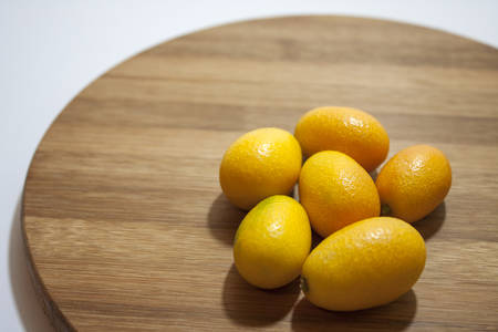 cumquat: Fresh fruit kumquat on the kitchen wooden board. Stock Photo