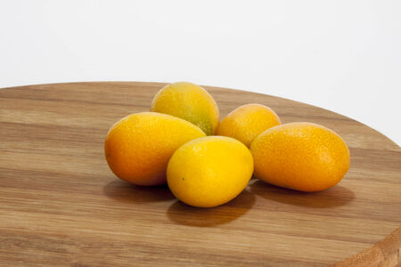 cumquat: Fresh fruit kumquat on the wooden board. Stock Photo