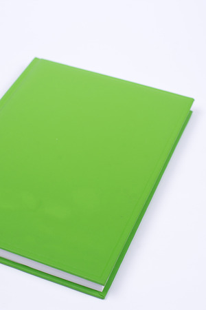 Green book with empty cover page over white background Imagens