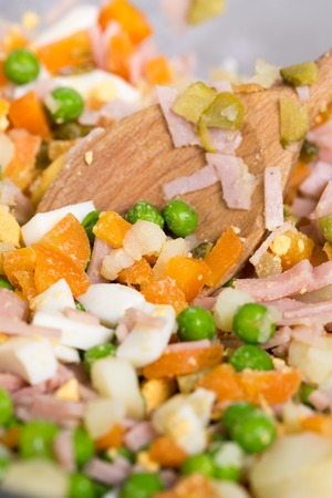 Mixing cooked fresh vegetables in russian salad Stock Photo