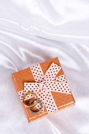 Flat lay gift box with bow and wedding rings on white satin