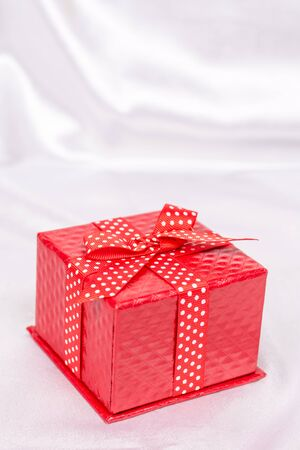 red gift box: Red gift box with bow on the white satin background Stock Photo