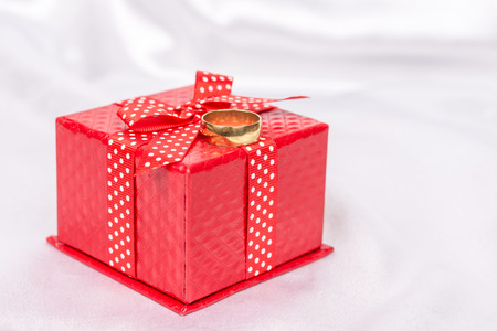 Red gift box with bow and golden wedding ring