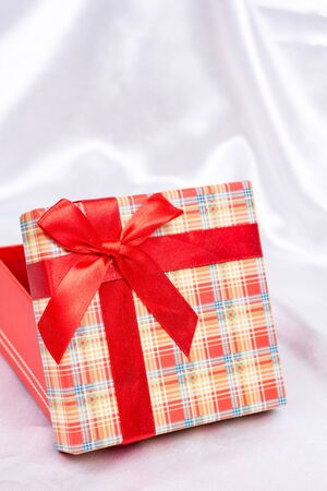 red gift box: Gift box with red bow over white satin
