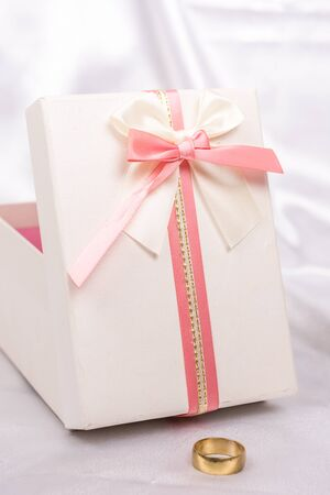 red gift box: White gift box with red bow over white satin