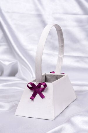 pink satin: Purple bow on white flower box on the white satin. Beautiful wedding background invitations.