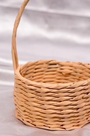 Woven basket for flower arrangement over white satin. Beautiful background for romantic wedding birthday invitations. Stock Photo