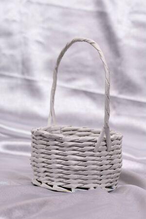 White woven basket for flower arrangement over white satin