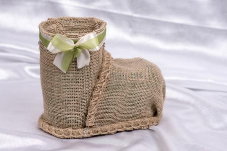 Brown retro rustic woven basket over white satin Stock Photo