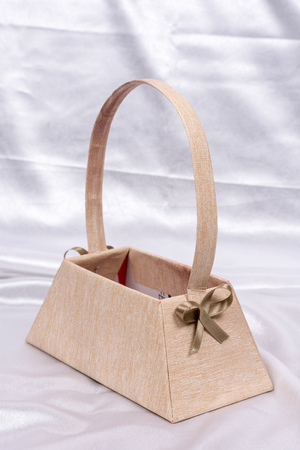 Paper basket for flower arrangement with red bow