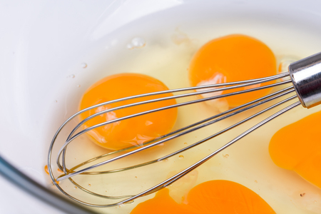 Mixed whisked eggs with wire isolated over white Stock Photo