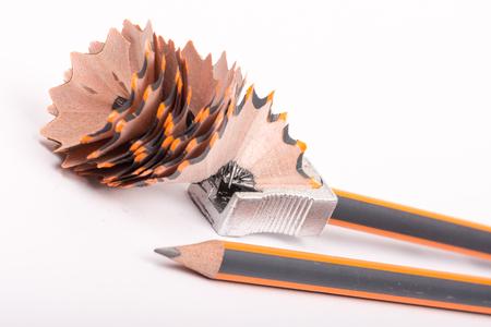 Afilando el lápiz de grafito de madera sobre el fondo blanco. Foto de archivo