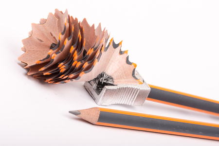 Sharpening wooden graphite pencil over white background.
