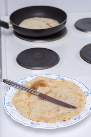 roasting pan: Frying pancakes on the stove macro food sweets Stock Photo