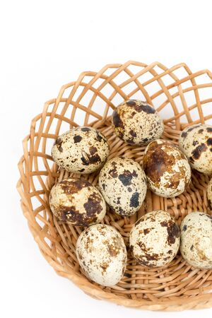 Quail eggs in the wooden basket over white background