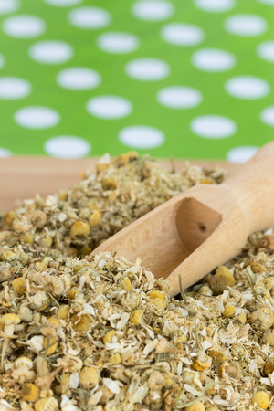 loose leaf: Wooden measuring spoon in dry chamomile tea Stock Photo