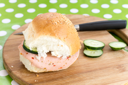 Salami sandwich and cucumber on the cutting board Stock Photo