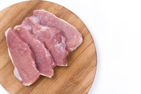 raw: Three raw pork chops on the kitchen wooden board.
