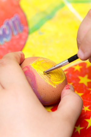 Childrens Hand coloring Easter egg with brush and tempera.