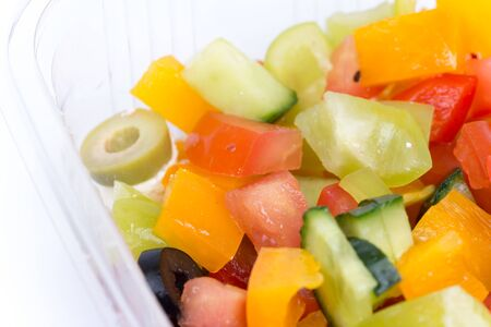 Greek salad in plastic box isolated over white. Stock Photo