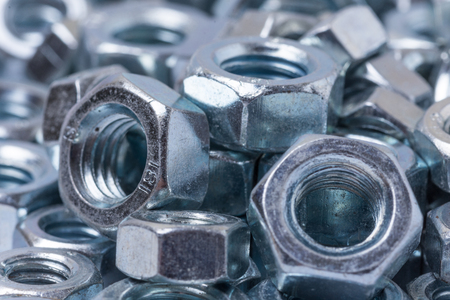 Pile of metal grey nuts in macro close up image.