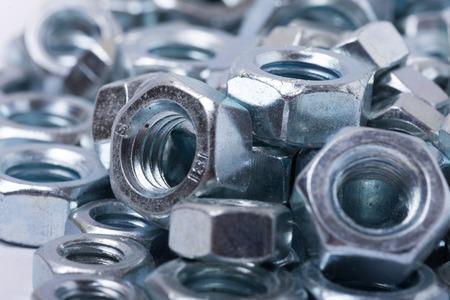 Pila de nueces de metal gris en macro close up image.
