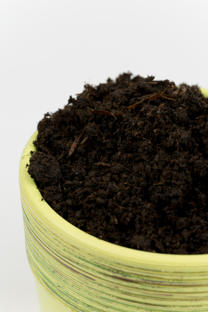 Ceramic flowerpot with soil on a white background.