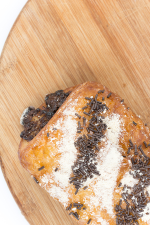 Chocolate croissant on a wooden board with copy space