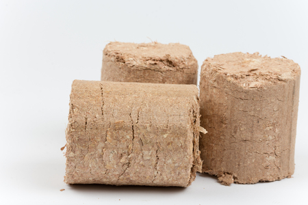 briquettes: Three wooden briquettes made of pressed sawdust.