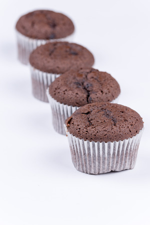 Brown chocolate muffins arranged over white background.