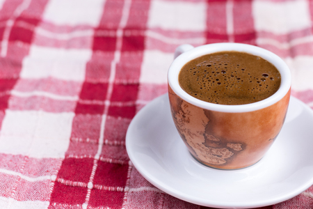 filled roll: Cup of coffee over red and white tablecloth. Stock Photo