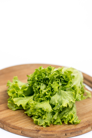 Green fresh raw lettuce isolated on the wooden board.