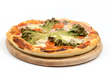 Baked round pizza with fresh lettuce and tomato with copy space. Stock Photo