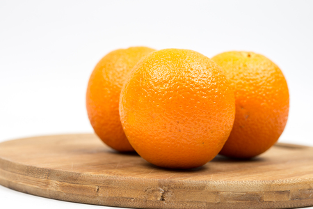 Three oranges on the wooden board with white background copy space. Stock Photo