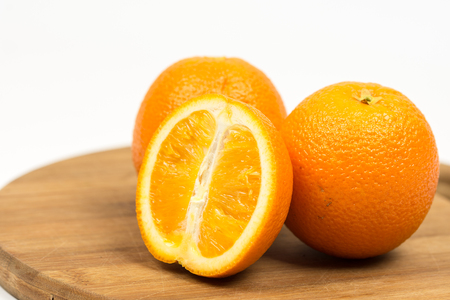 Sliced oranges on the wooden board isolated over white with copy space.