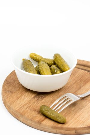 marinated gherkins: Small pickles in the white bowl and pickle on the fork.