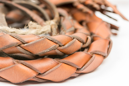 flogging: Leather whip isolated over white background closeup macro.