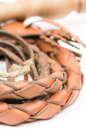 bdsm: Leather whip isolated over white background closeup macro.