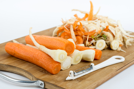 Peeled carrots and parsnips on the cutting wooden board. Stock Photo