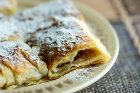 Apple pie sliced on the plate with powdered sugar. Stock Photo
