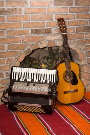 Accoustic guitar on the brick wall and accordion