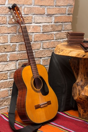 Accoustic guitar by the brick wall background