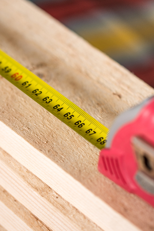 perspectiva lineal: Medidor de construcción en la pila de tablones de madera.